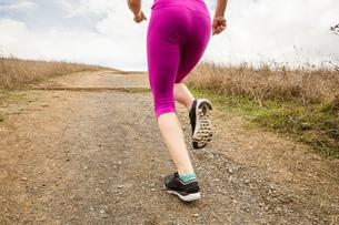 Waist down rear view of female runner running up dirt trackの写真素材 [FYI03573731]