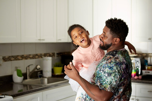 Father carrying daughter in kitchenの写真素材 [FYI03573863]