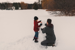 Father and daughter making snowmanの写真素材 [FYI03573892]