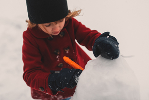 Girl using carrot for snowman's noseの写真素材 [FYI03573893]
