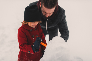 Father and daughter making snowmanの写真素材 [FYI03573894]