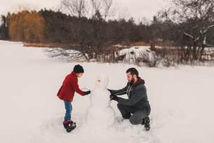 Father and daughter making snowmanの写真素材 [FYI03573896]