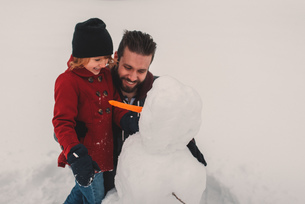 Father and daughter making snowmanの写真素材 [FYI03573898]