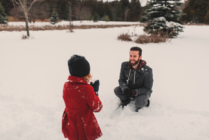 Girl throwing snowball at her fatherの写真素材 [FYI03573904]