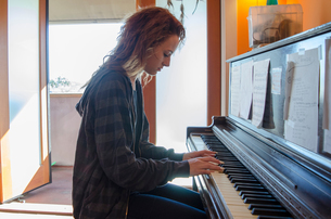 Teenager playing piano at homeの写真素材 [FYI03573925]