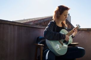 Teenager playing guitar on roof terraceの写真素材 [FYI03573927]
