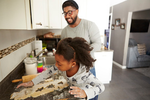 Father and daughter baking cookies togetherの写真素材 [FYI03573940]