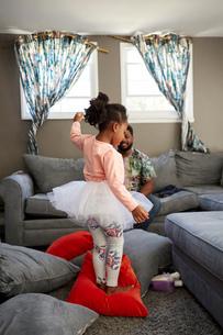 Girl in tutu dancing on cushions for fatherの写真素材 [FYI03573973]
