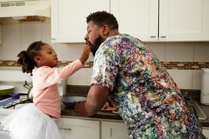 Girl feeding father in kitchenの写真素材 [FYI03573977]