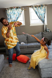 Girl in fairy costume casting spell on father in living roomの写真素材 [FYI03573978]