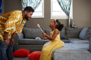 Man playing with daughter in fairy costume in living roomの写真素材 [FYI03573980]