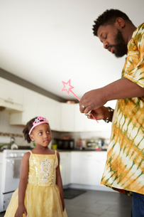 Mature man repairing fairy wand for daughter in kitchenの写真素材 [FYI03573981]