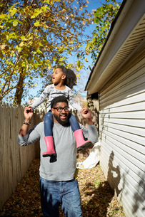 Mature man carrying daughter on shoulders by residential garageの写真素材 [FYI03573989]