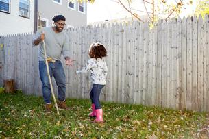 Girl handing autumn leaf to her father in gardenの写真素材 [FYI03573990]