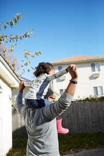 Mature man carrying daughter on shoulders in gardenの写真素材 [FYI03573991]