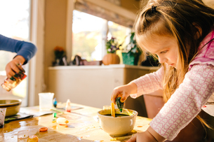 Girl doing science experiment, dropping green liquid into bowlの写真素材 [FYI03574018]