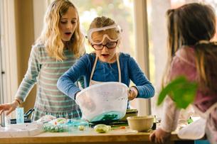 Girls doing science experiment, mixing green liquid in bowlの写真素材 [FYI03574024]