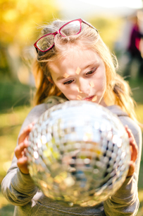 Girl in sunlit garden gazing at disco ballの写真素材 [FYI03574026]