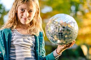 Portrait of girl in garden holding disco ballの写真素材 [FYI03574029]