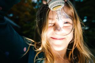 Portrait of girl holding illuminated lightbulb in garden at duskの写真素材 [FYI03574039]