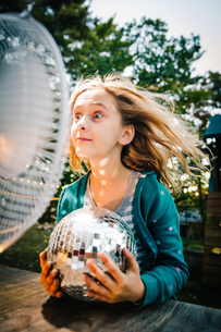 Girl pulling face in front of windy electric fan at garden tableの写真素材 [FYI03574041]