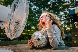 Girl screaming in front of windy electric fan at garden tableの写真素材 [FYI03574043]