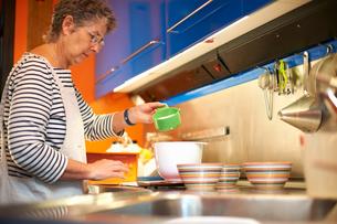 Senior woman in kitchen, measuring ingredients into mixing bowlの写真素材 [FYI03574114]