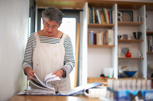Senior woman in kitchen, looking through fileの写真素材 [FYI03574117]