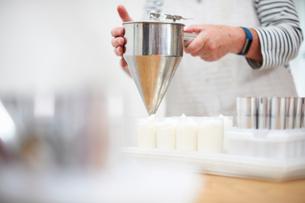 Senior woman in kitchen, using pancake funnel to dispense cream, homemade cosmetics, into pots, midの写真素材 [FYI03574121]