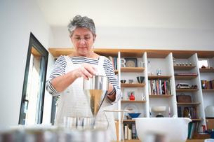 Senior woman in kitchen, using pancake funnel to dispense cream, homemade cosmetics, into pots, midの写真素材 [FYI03574125]