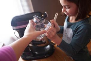 Young girl using food mixer, mother handing daughter measuring jugの写真素材 [FYI03574130]