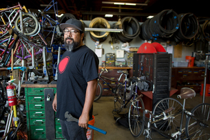 Portrait of mature man holding wrench in bicycle workshopの写真素材 [FYI03574196]