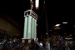 Portrait of female metalsmith steadying chain hoist in workshopの写真素材 [FYI03574197]