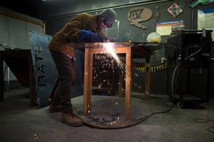 Male metalsmith plasma cutting metal at workbenchの写真素材 [FYI03574198]