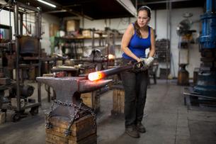 Female metalsmith turning red hot metal rod on workshop anvilの写真素材 [FYI03574219]