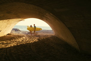 Surfing couple in underpass at Newport Beach, California, USAの写真素材 [FYI03574245]