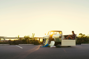 Young female surfer looking at smartphone in back of pickup truck at Newport Beach, California, USAの写真素材 [FYI03574248]
