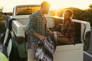 Surfing couple in back of pickup truck at sunset at Newport Beach, California, USAの写真素材 [FYI03574250]