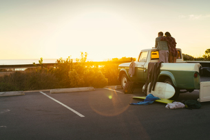 Rear view of couple in back of pickup truck watching sunset at Newport Beach, California, USAの写真素材 [FYI03574251]