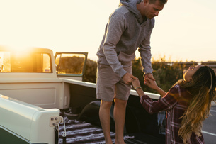 Couple holding hands at back of pickup truck at Newport Beach, California, USAの写真素材 [FYI03574252]