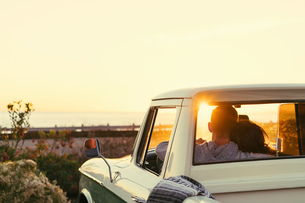 Rear view of couple in pickup truck watching sunset at Newport Beach, California, USAの写真素材 [FYI03574254]