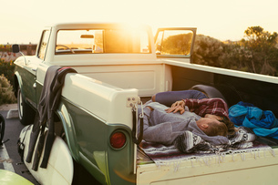 Surfing couple lying in back of pickup truck at Newport Beach, California, USAの写真素材 [FYI03574255]