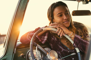 Young woman leaning against steering wheel in pickup truck at Newport Beach, California, USAの写真素材 [FYI03574257]
