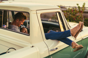 Romantic couple in pickup truck with legs out of window at Newport Beach, California, USAの写真素材 [FYI03574261]