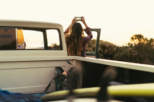 Rear view of  young woman with pickup truck photographing coast at Newport Beach, California, USAの写真素材 [FYI03574264]