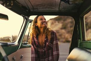 Happy young woman at pickup truck door at Newport Beach, California, USAの写真素材 [FYI03574266]