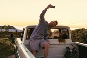 Man taking smartphone selfie with girlfriend in back of pickup truck at Newport Beach, California, Uの写真素材 [FYI03574268]