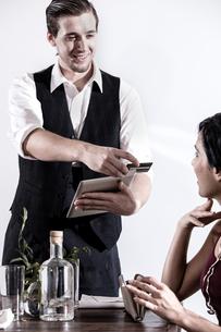 Waiter serving diner in restaurant, waiter using digital tabletの写真素材 [FYI03574283]