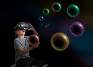 Young boy wearing virtual reality headset, holding planet in hand, digital compositeの写真素材 [FYI03574306]