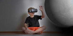 Young boy sitting cross legged, wearing virtual reality headset, reaching out to touch planet, digitの写真素材 [FYI03574308]